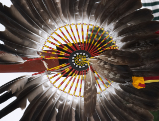 Close up of an American Indian feathery headdress with yellow and red beaded patter in the middle