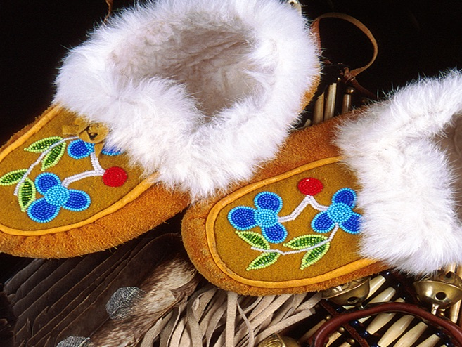 pair of tan moccasins with fuzzy insides and blue beaded flowers on the tops