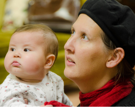 Infant child with chubby cheeks being held by adult wearing black beret and red scarf