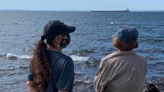 Roxanne Gould and her mother making an offering of asema (tobacco) at Lake Superior with a ship in the distance.