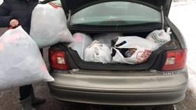 open car trunk filled with plastic bags of clothing
