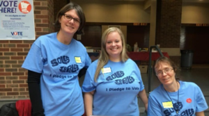 """Sandra van den Bosse and two Social Work students, all 3 wearing a blue t-shirt that reads """"I pledge to vote"""""""