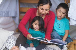 American Indian mother and children reading a book together