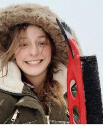 Alyssa Koktavy smiles with a fuzzy winter hood over her head and an ice scraper in her hand