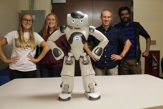robot with hands on hips stands in front of 4 students replicating the robot's pose