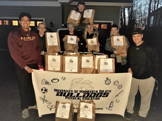 7 UMD Physical Education students displaying bags of resources they collected to distribute to community members in need.