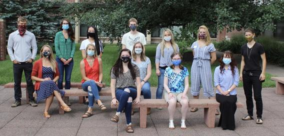 13 masked Master of Psychological Science students seated and standing in an outdoor setting
