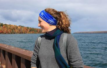 Hillary Olsen looking off to the side and smiling with Lake Superior and fall foliage in the background