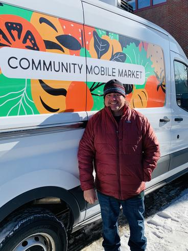 Karl Becker in front of the community mobile market van