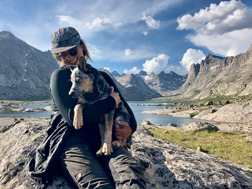 Simone Anzion hugs a dog in a mountainous outdoor location