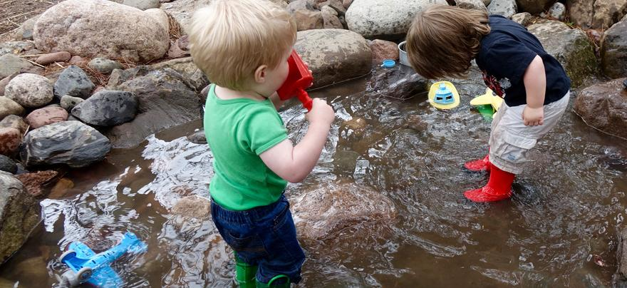 Children playing with water toys in a stream