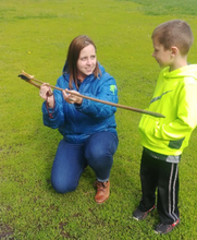 Elizabeth Reetz showing a young child a wooden spear