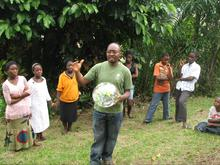 Edwin Nganji holding a globe in front of several young students