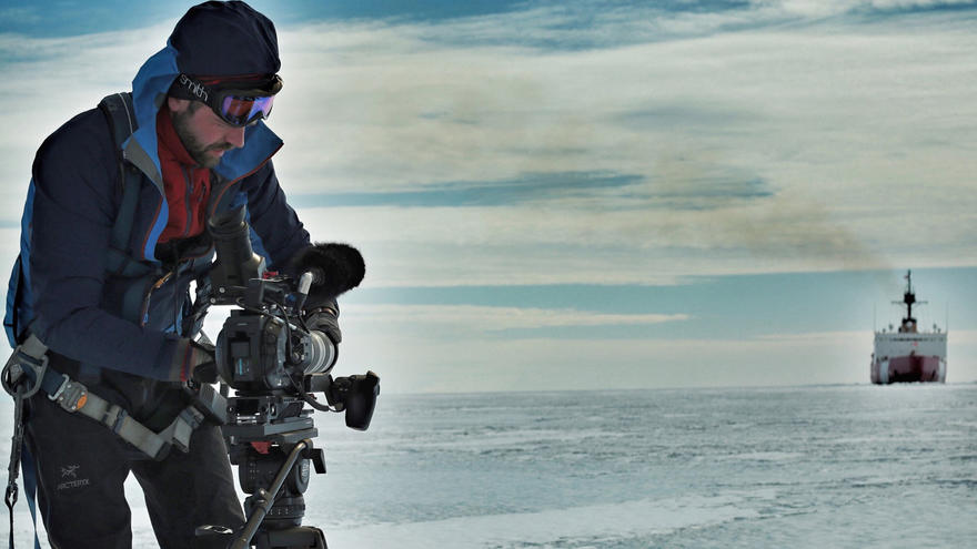 JJ Kelley adjusts his camera in an icy landscape with a ship in the distance