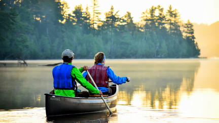 two people paddling a canoe on a scenic lake
