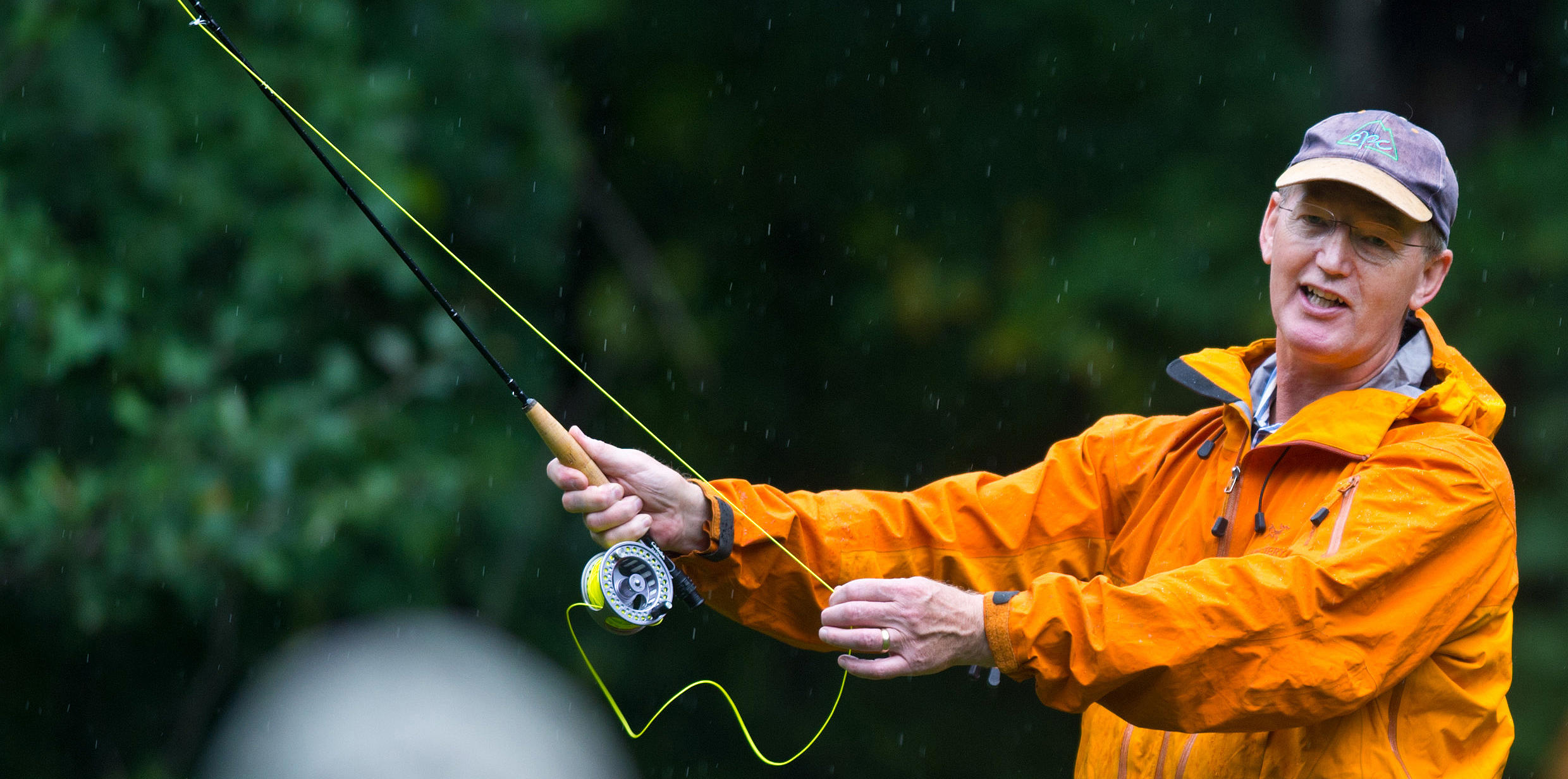 Man in orange rain coat demonstrating fly-fishing technique