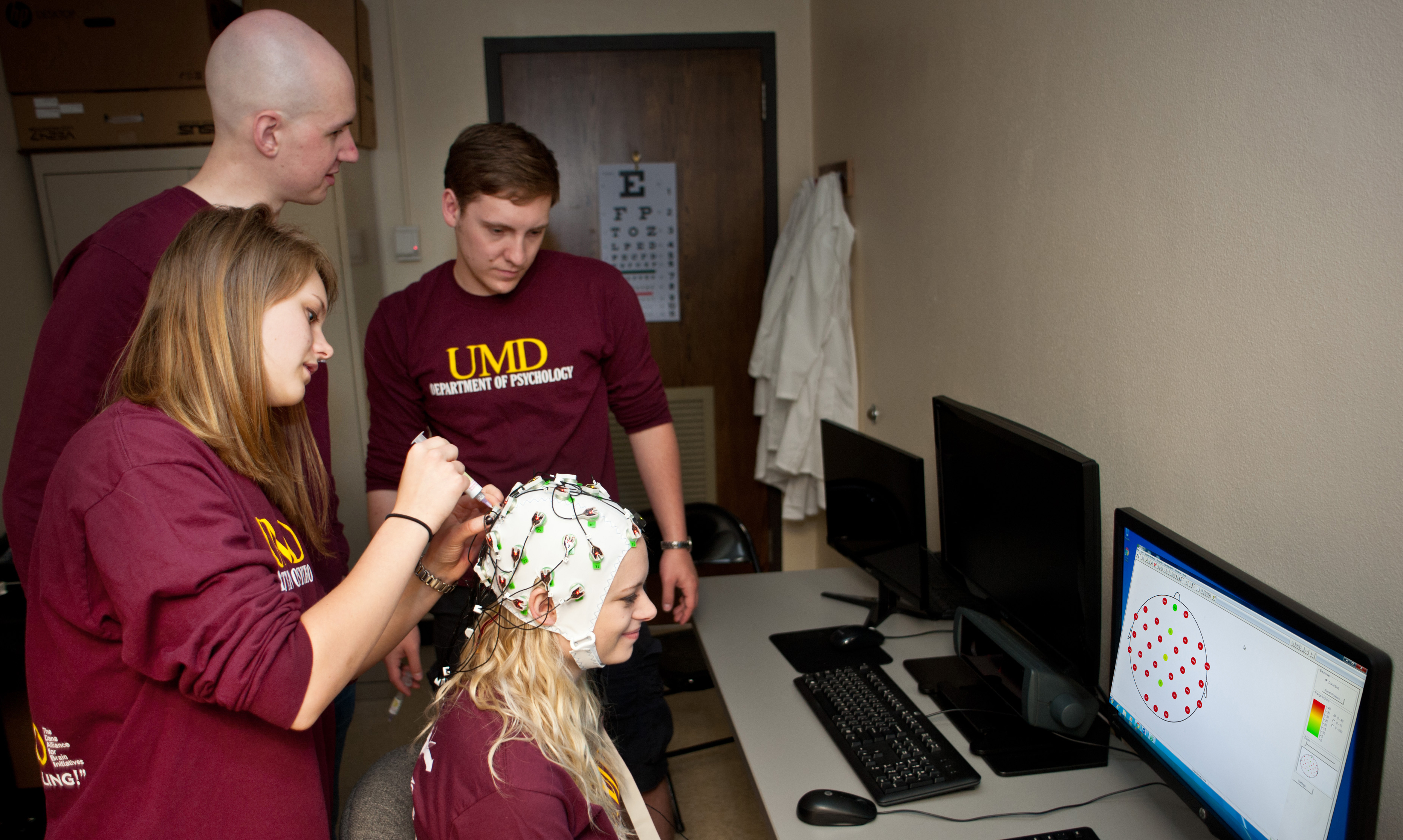 Psychology students demonstrating use of skull cap to read brain activity